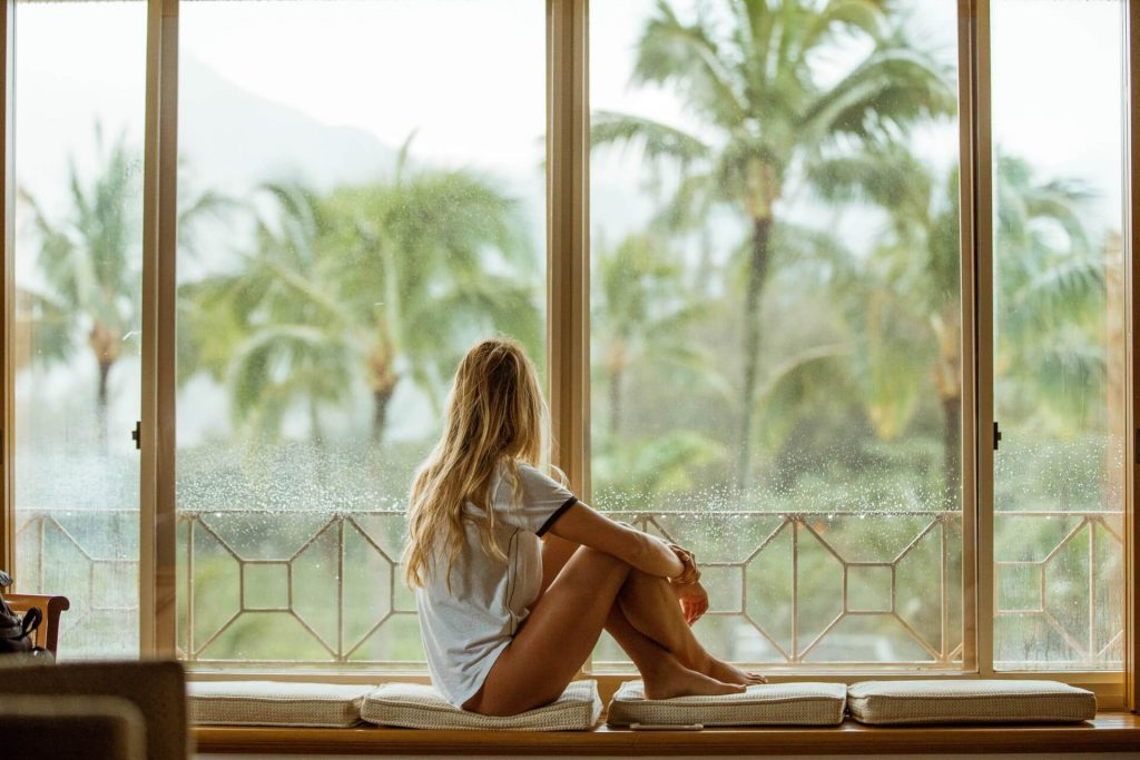 Woman sitting in front of the large window and looking at palm trees