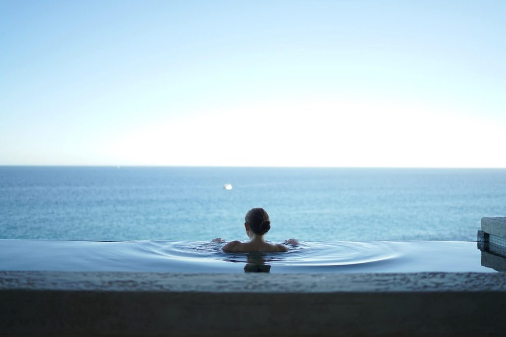 woman in a pool looking at the sea