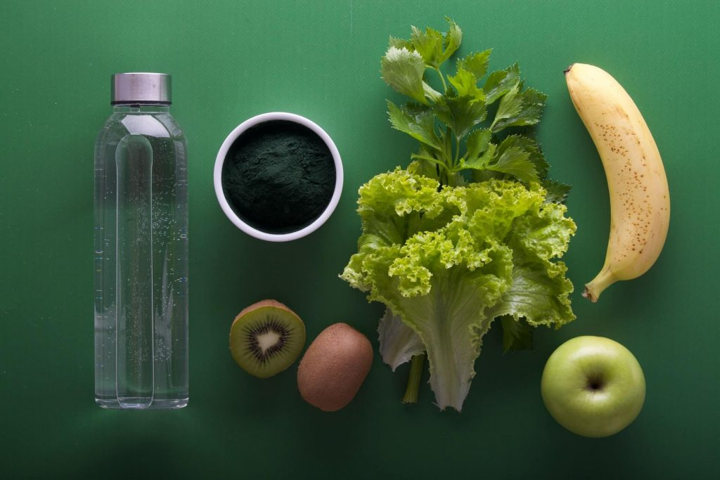 Kale, a banana, green tea powder, a kiwi, an apple, and a bottle of water on the green surface