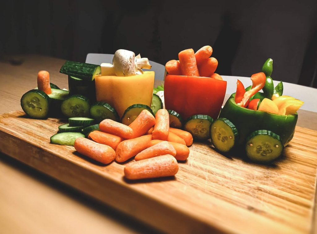 Cut carrots, cucumbers, a mushroom, and peppers on the wooden plank